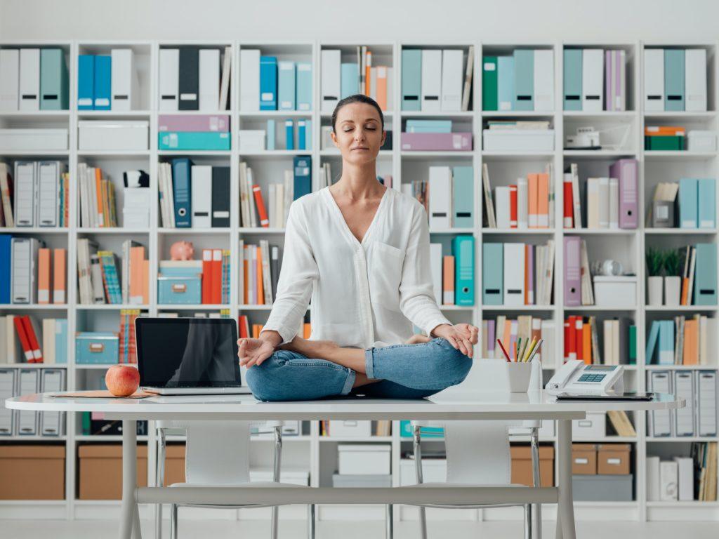 Woman practicing meditation on a desk